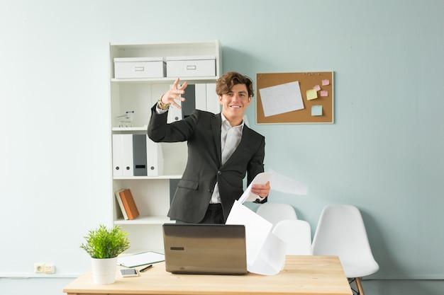 Мужчина в костюме подбрасывает листы бумаги в офисе