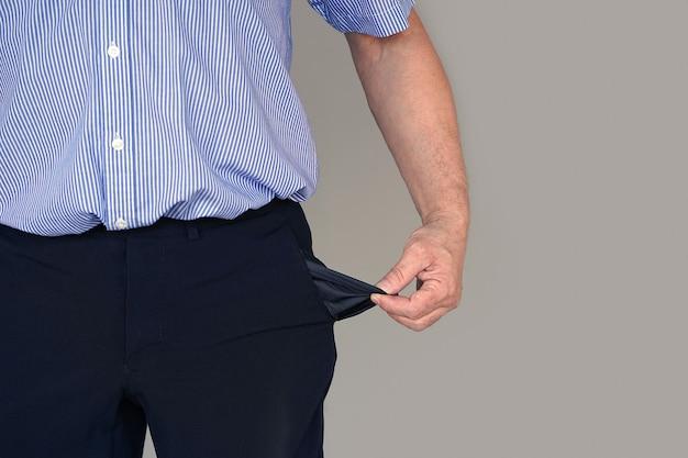 スーツを着た男性がズボンのポケットを裏返し、空を見せています。危機、失業、破産の概念