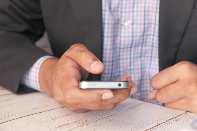 Человек в костюме с помощью смартфона на офисном столе