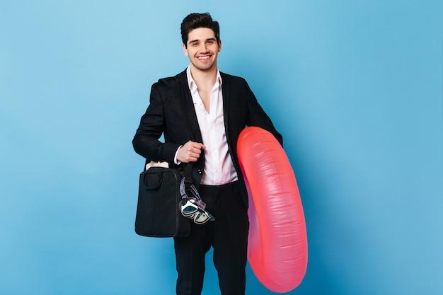 ノートパソコンのバッグを持ったスーツの男は、ダイビングマスクとゴムの指輪を持っています。男は休みたい。