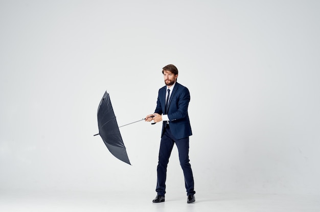 雨から傘の天候保護とスーツを着た男