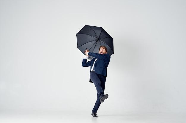 Мужчина в костюме с зонтиком от непогоды от дождя