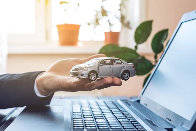 Человек в костюме работает с ноутбуком, держа в руках автомобиль. концепция поиска и покупки авто в интернете