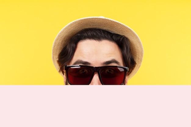 Человек в солнечных очках и панамской шляпе держит пустой знамя