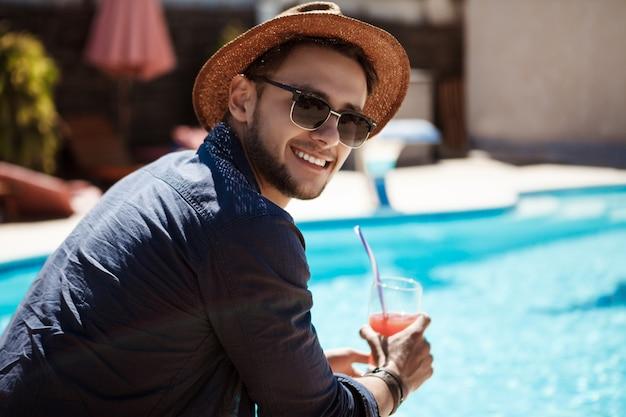 サングラスと帽子を飲んでカクテル、プールのそばに座っている男