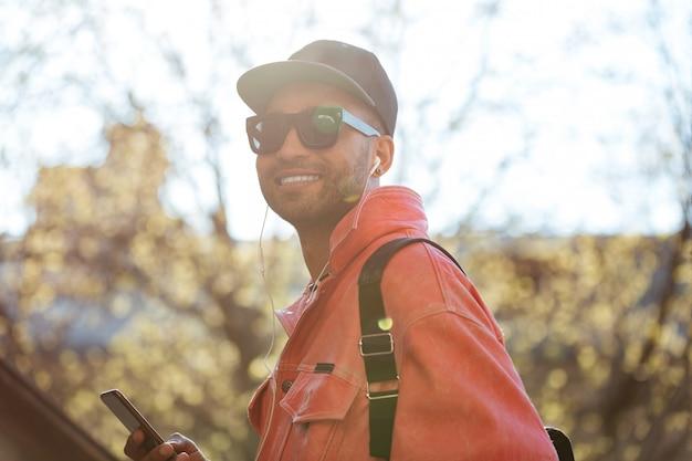 Человек в темных очках слушает музыку с мобильным телефоном и наушниками
