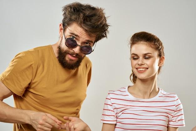 コミュニケーションの楽しい友情のライフスタイルで女性の隣にサングラスをかけた男性。