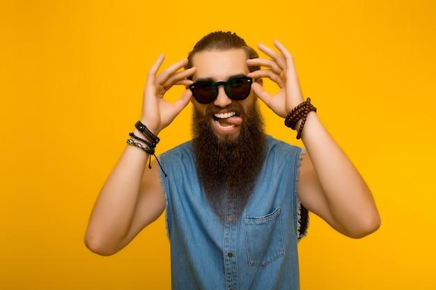 노란색 배경에 고립 된 혀를 보여주는 선글라스에 남자.