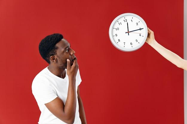 驚いた男は白いtシャツの孤立した背景で彼の時計を見て