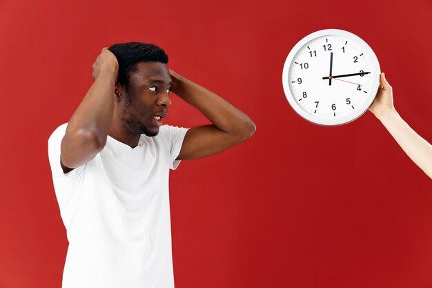 驚いた男は白いtシャツで彼の時計を見て