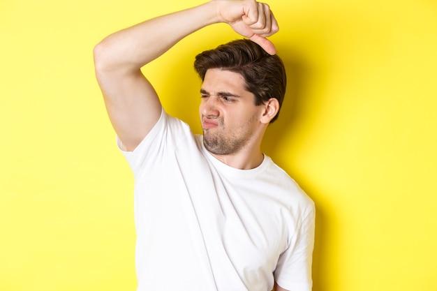 Мужчина в поту, нюхающий свою подмышку, стоит в белой футболке и морщится от вонючей одежды.