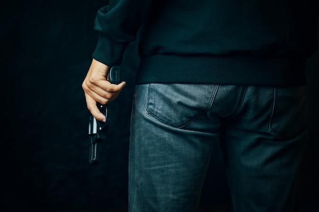 스웨터와 청바지를 입은 남자가 총을 들고 검은 배경 총기에 리볼버를 들고 있다.