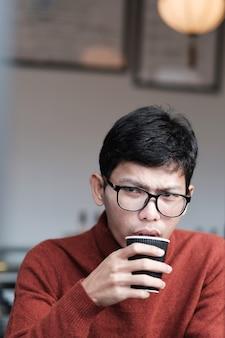 Мужчина в свитере пьет горячий кофе в ресторане