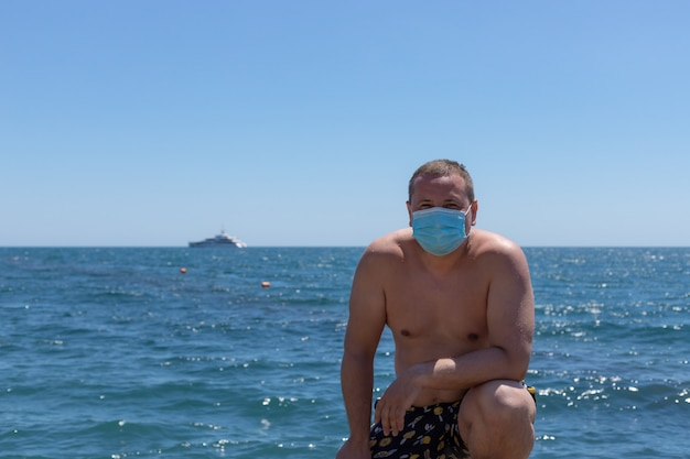 青い海のスイムショーツと防護マスクの男