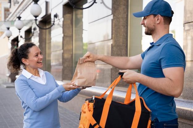 持ち帰り用の食べ物を届けるtシャツの男