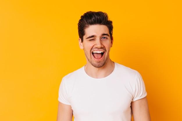 Мужчина в футболке в хорошем настроении подмигивает на фоне оранжевого пространства.