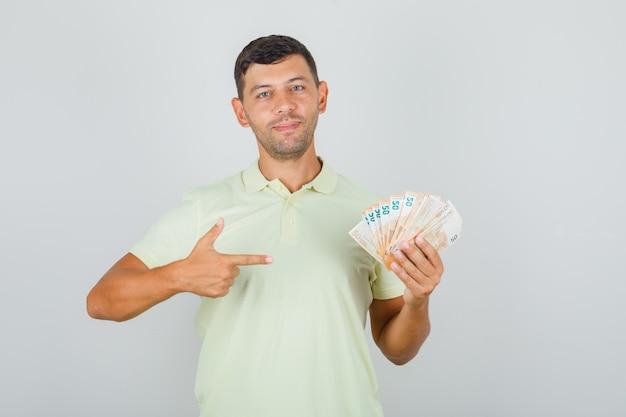 Человек в футболке указывая пальцем на банкноты евро и выглядит счастливым