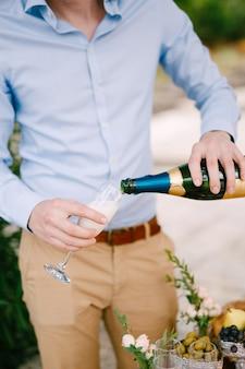 결혼식 근접 촬영 동안 유리에 샴페인을 붓는 파란색 셔츠에 남자