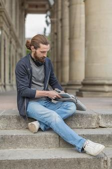 Человек в городе вытаскивает ноутбук