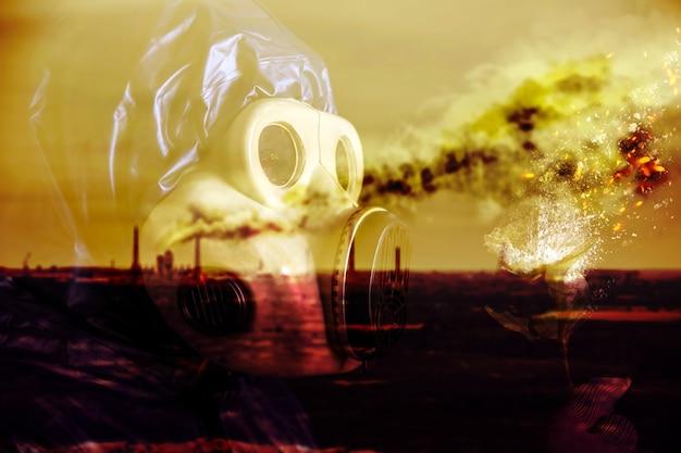花を持っている防毒マスクの男。自然の汚染。環境汚染。危険な原子力発電。生態学的災害。自然は燃えています。スモッグのある工場。