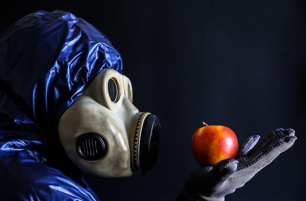 リンゴを保持しているガスマスクの男。放射線の影響。環境汚染。チェルノブイリの概念。危険な原子力発電。生態学的災害。