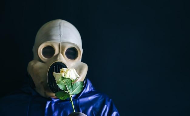 花を保持しているガスマスクの男。放射線の影響。環境汚染。チェルノブイリの概念。危険な原子力発電。生態学的災害。