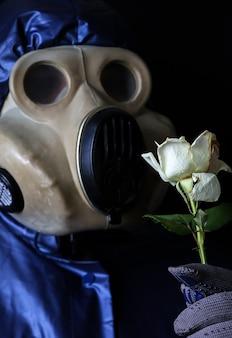 Человек в противогазе держит цветок. радиационное воздействие. загрязнение окружающей среды. чернобыльская концепция. опасная ядерная энергетика. экологическая катастрофа.