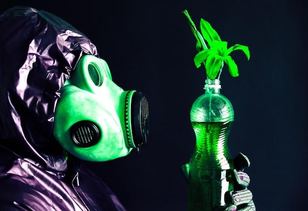 汚れた水と花とペットボトルを保持しているガスマスクの男。放射線の影響。環境汚染。チェルノブイリの概念。危険な原子力発電。生態学的災害。