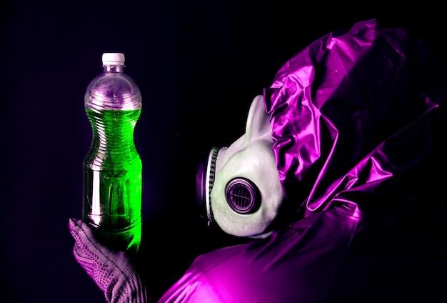汚れた水でペットボトルを保持しているガスマスクの男。放射線の影響。環境汚染。チェルノブイリの概念。危険な原子力発電。生態学的災害。