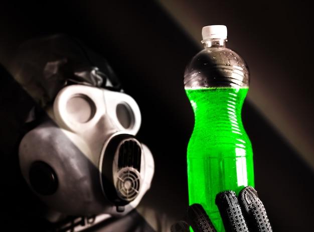 녹색 물이 든 플라스틱 병을 들고 가스 마스크를 쓴 남자. 방사선 영향. 환경 오염. 위험한 원자력. 생태 재앙입니다.