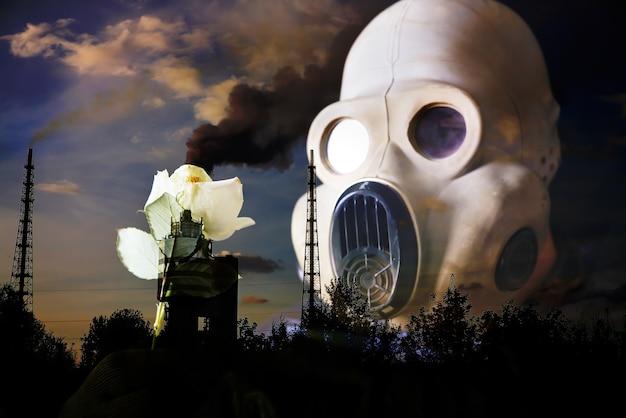 黄色の明るい花を保持している防毒マスクの男。放射線の影響。環境汚染。チェルノブイリの概念。危険な原子力発電。生態学的災害。煙のある工場パイプ。