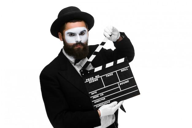 Человек в образе мима с кинохлопушкой