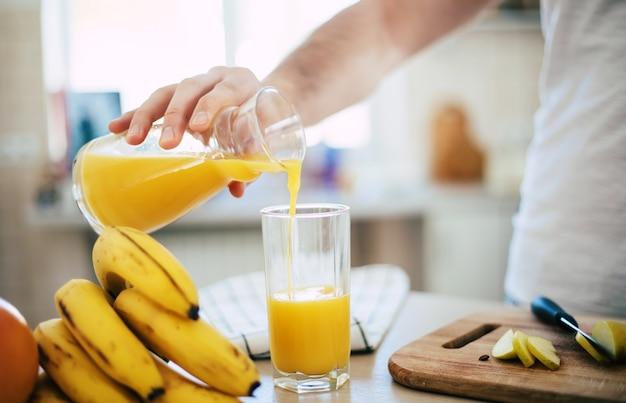 Человек на кухне пьет апельсиновый сок