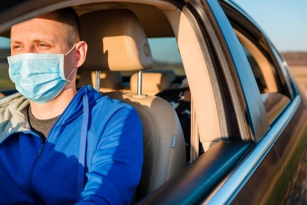 Человек в медицинской маске в машине. коронавирус, болезнь, инфекция, карантин, ковид-19