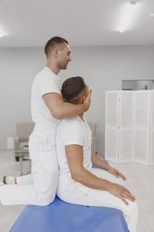 Мужчина в медицинском кабинете. физиотерапевт восстанавливает спину.