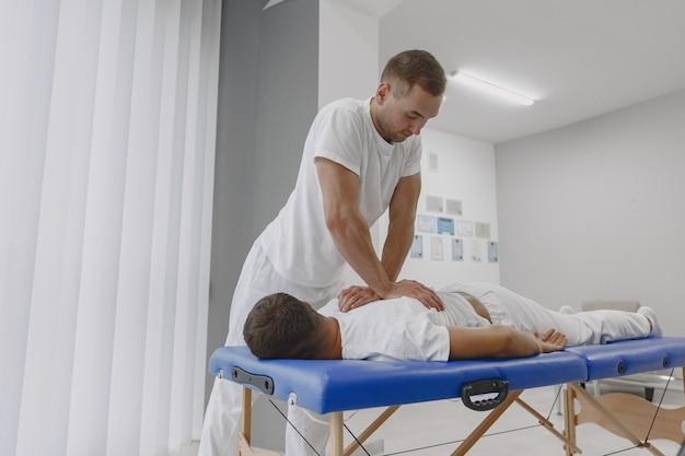 의료 사무실에있는 남자. 물리 치료사가 다시 회복하고 있습니다.
