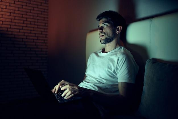Человек в комнате ночью смотрит фильмы отдыхает