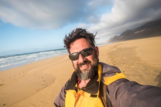Человек в дикой природе на пляже делает селфи