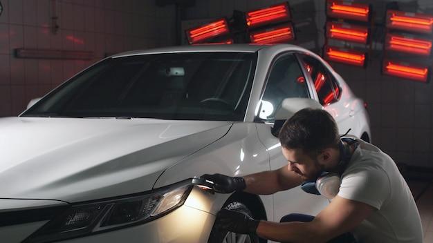 Человек в мастерской проверяет качество краски автомобиля с помощью фонарика