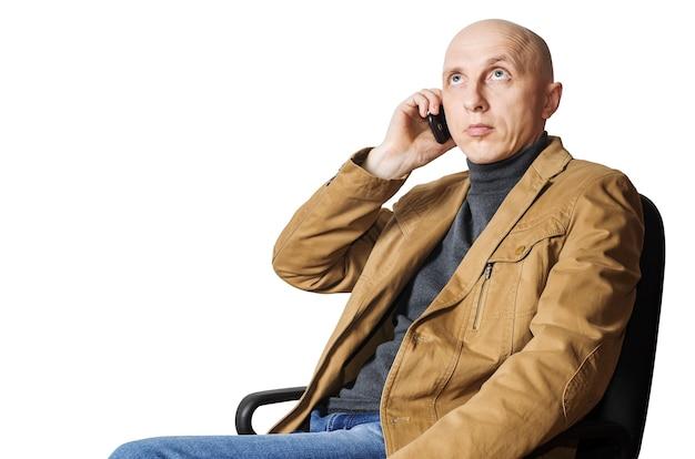 노란색 재킷을 입은 남자가 사무실 의자에 앉아있는 동안 휴대 전화로 전화하고 있습니다.
