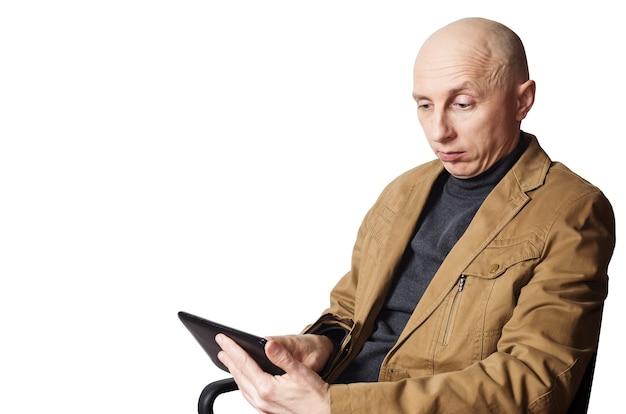 사무실 의자에 앉아 태블릿 컴퓨터를보고 노란색 재킷을 입은 남자