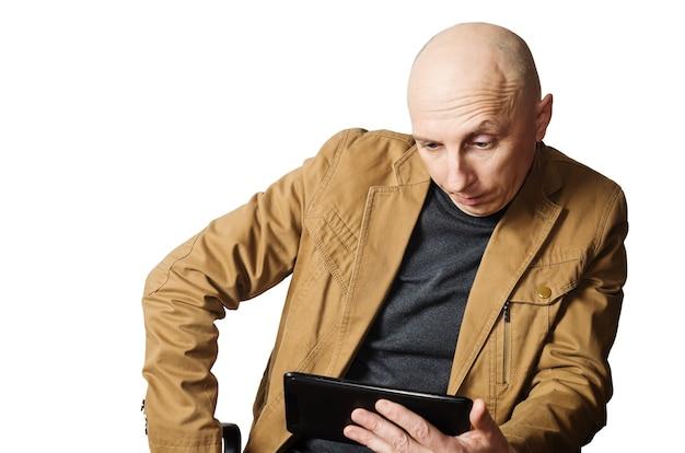 태블릿 컴퓨터를보고 노란색 재킷을 입은 남자가