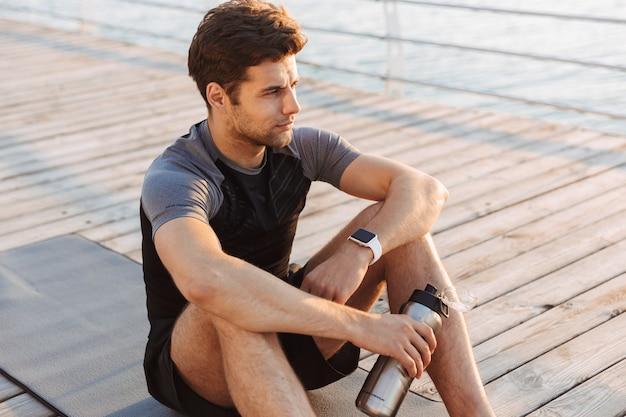 朝の海辺で、木製の桟橋でのトレーニングの後、魔法瓶マグとマットの上に座っているトラックスーツの男