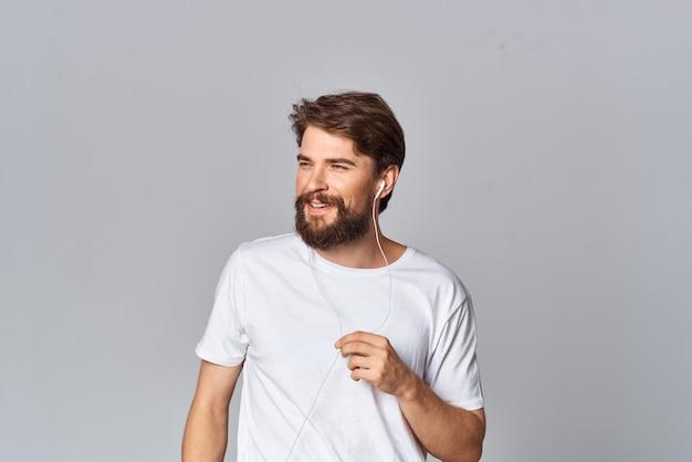 Человек в футболке с бородой в студии позирует на светлом фоне
