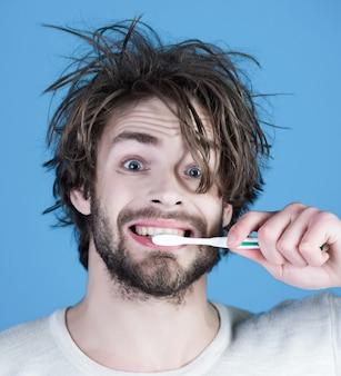 下着ブラシの歯の朝の洗濯の男は、日常生活の衛生歯を白くする口腔病学と歯科治療の幸せな朝の男を青で目覚めさせます