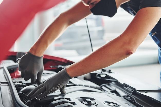 Человек в форме и черной защитной маске работает с разбитым автомобилем. концепция автосервиса