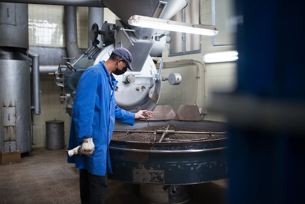 볶은 커피의 품질을 확인하는 유니폼을 입은 남자. 로스팅 장비에서 작업하는 커피 로스터. 마스크와 제복을 입은 남자 기계 기기 작업