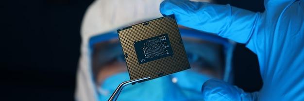 Человек в форме держит микропроцессор с щипцами