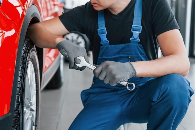 Человек в форме сидит с гаечным ключом в руке возле сломанного автомобиля. концепция автосервиса