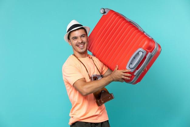 파란색에 큰 빨간 가방을 들고 휴가에 남자